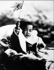 Emperador Hirohito de niño sosteniendo la bandera del ejército imperial en 1902.